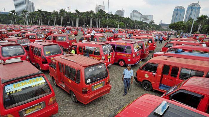 Para sopir angkutan kota Koperasi Wahana Kalpika (KWK) memarkirkan kendaraan di kawasan Monumen Nasional saat berunjuk rasa di depan Balaikota Jakarta, Selasa (22/3). Selaian menuntut penghapusan angkutan umum berbasis aplikasi karena turut mempengaruhi pendapatan para sopir angkutan kota, mereka juga menuntut pencabutan suret edaran tentang izin perpanjangan trayek dan izin usaha.  Kompas/Raditya Helabumi (RAD) 22-03-2016
